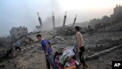 Người dân Palestine thu nhặt đồ đạc từ đống đổ nát của căn nhà bị phá hủy bởi một cuộc không kích của Israel vào thứ Ba tại dải Gaza.