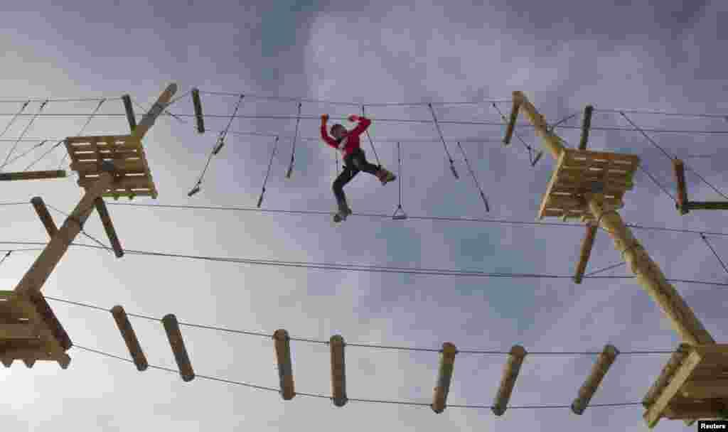 Một phụ nữ đang đi trên dây trong lễ khai mạc một công viên với trò chơi đi dây trong Khu Trượt tuyết Shimbulak trong dãy núi Thiên Sơn, bên ngoài thành phố Almaty của Kazakhstan. Người thiết kế nói công viên mới mở này là công viên dây cao nhất thế giới được dựng trên những giá đỡ nhân tạo. (Reuters)