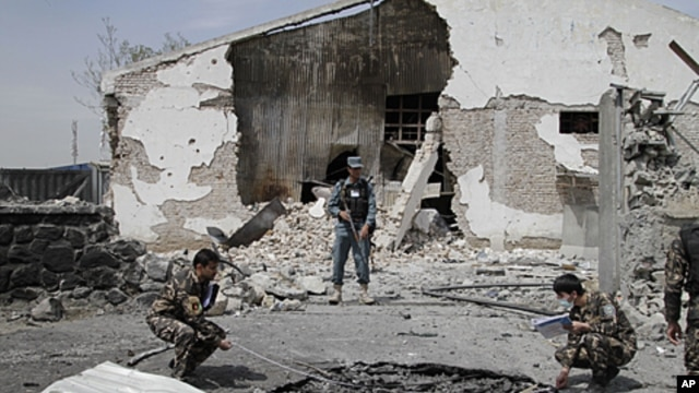 Afghan investigation team members assess the damage caused at the scene of a militant attack in Kabul, Afghanistan, May 2, 2012.