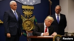 U.S. President Donald Trump signs a revised executive order for a U.S. travel ban on Monday, leaving Iraq off the list of targeted countries, at the Pentagon in Washington.