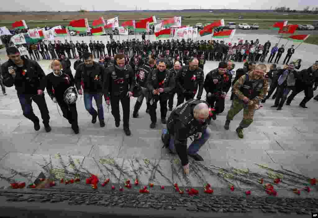 Para pengendara motor besar Rusia meletakkan bunga di tempat peringatan tentara Soviet yang gugur pada Perang Dunia II di Minsk, Belarusia.