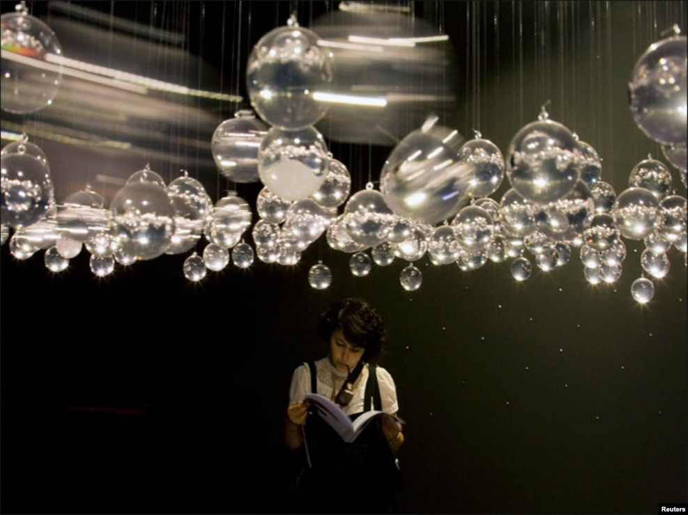وینس میں منعقدہ بین الاقوامی آرٹ نمائش کے دوران ایک خاتون نمونوں کی تفصیل کا مطالعہ کررہی ہیں