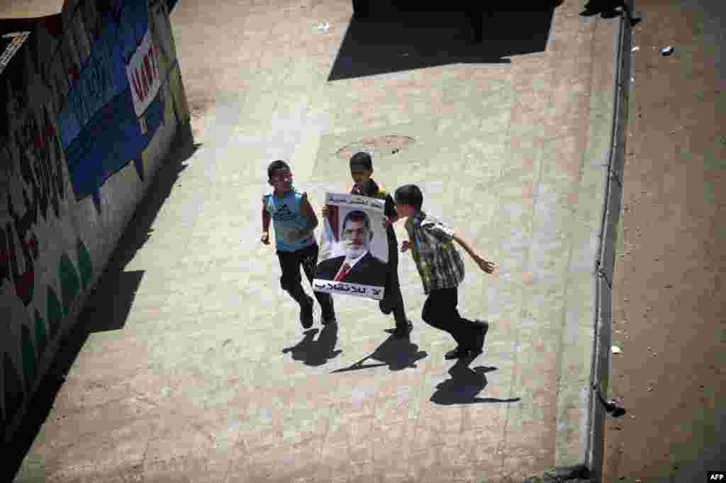 Egyptian children with portrait of Morsi run during a demonstration in support of the ousted president in Cairo, August 9, 2013.