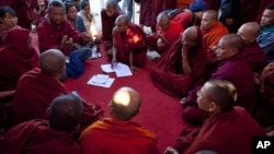 Activist known as Ko Kyaw, left background in blue pants, gestures during a meeting with protesting Buddhist monks who occupy the office entrance to the Chinese copper mine company Wan Bao Co. Ltd in northwestern Myanmar, Wednesday, Nov 28, 2012.