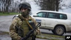 FILE - A Ukrainian soldier guards OSCE observers near the village of Shyrokyne, eastern Ukraine, April 19, 2015.
