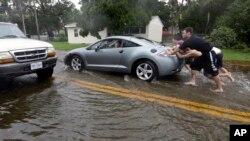 Warga mendorong mobil yang mogok terkena banjir akibat Badai Matthew di Florida (7/10). (AP/Eric Gay)