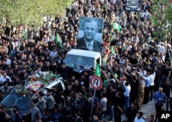 Mourners take the coffin of former Iraq President Jalal Talabani, seen in the poster, for burial during his funeral procession in Sulaimaniyah, 260 kilometers (160 miles) northeast of Baghdad, Iraq, Oct. 6, 2017.