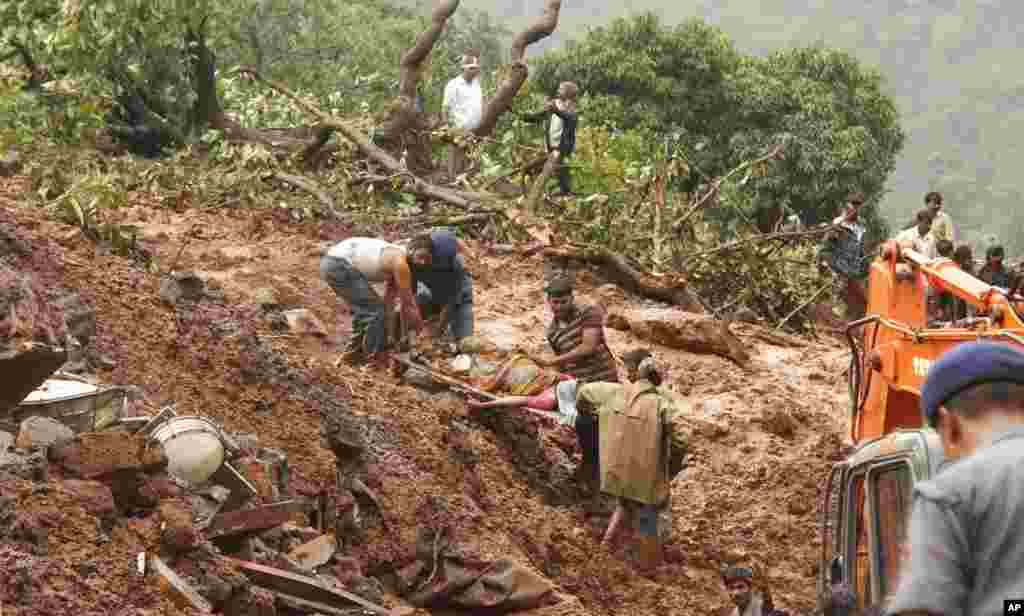 Rescue workers remove the body of a victim in Malin village, Wednesday, July 30, 2014.