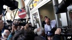 Lefkoşa'da bir banka personeli müşterilere kapıyı açarken