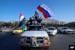 Syrian government supporters wave Syrian, Iranian and Russian flags as they chant slogans against U.S. President Trump during demonstrations following a wave of U.S., British and French military strikes to punish President Bashar al-Assad for suspected chemical attacks against civilians, in Damascus, Syria, April 14, 2018.