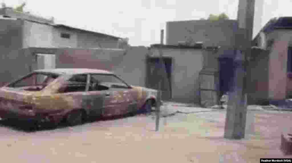 Burned car and buildings from a Boko Haram attack near Maiduguri, December 2013.