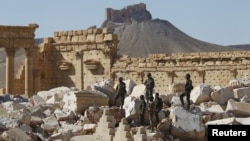 Syrian army soldiers stand on the ruins of the Temple of Bel in the historic city of Palmyra, in Homs Governorate, Syria, April 1, 2016. The Fakhreddin's Castle is seen in the background.