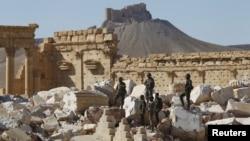 ທະຫານ ຊີເຣຍ ຢືນຢູ່ເທິງຊາກຫັກພັງຂອງວັດ Bei ໃນເມືອງປະຫວັດສາດ Palmyra, ແຂວງ Homs Governorate, ປະເທດ ຊີເຣຍ. 1 ເມສາ, 2016.