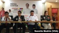 Direktur Hukum dan Advokasi Tim Kampanye Nasional (TKN) Jokowi-Ma'ruf, Ade Irfan Pulungan (jaket putih) bersama timnya saat menggelar konferensi pers di Posko Cemara di Jakarta, Selasa (26/3/2019) (foto: VOA/Sasmito Madrim)