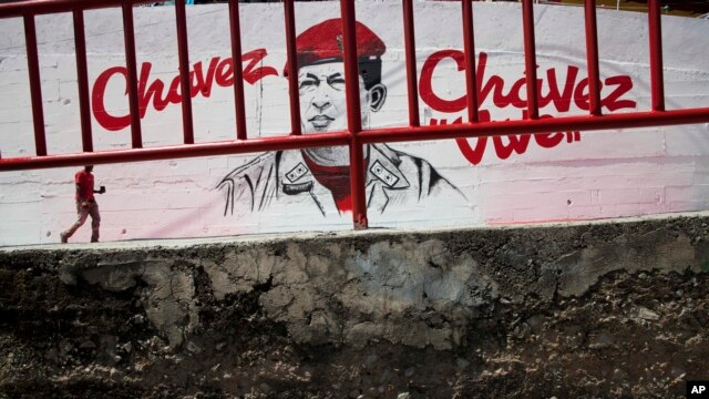 A man walks in front of a mural of Venezuela's late President Hugo Chavez in Caracas, Venezuela, March 4, 2014.