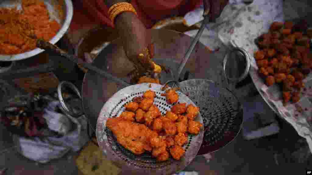 Une femme vend des baignets qu'elle prépare avec ses mains. Des maladies contagieuses peuvent être évitées avec le lavage regulier des mains. (AP Photo/Saurabh Das)