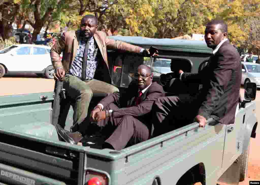 Douglas Mahiya, le secrétaire des anciens combattants du Zimbabwe est escorté par des détectives alors qu'il arrive à la cour de Harare, Zimbabwe, le 29 juillet 2016.