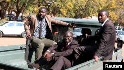 Douglas Mahiya, le secrétaire des anciens combattants du Zimbabwe escorté par des détectives alors qu'il arrive à la cour de Harare, Zimbabwe, 29 juillet 2016.