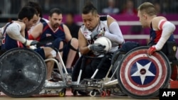 Japan's Shin Nakazato (C) holds onto the ball as Chuck Aoki of the US (L) closes in during the bronze medal Wheelchair Rugby match between USA and Japan, in London, September 9, 2012.