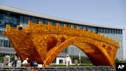 "Workers install wires on a Golden Bridge of Silk Road structure outside the National Convention Center, the venue for the Belt and Road Forum for International Cooperation, in Beijing, April 18, 2017. Starting Sunday, Vladmir Putin of Russia, Recep Tayyip Erdogan of Turkey and Spain's Mariano Rajoy are among those attending a summit to discuss Xi's ""One Belt, One Road"" infrastructure investment program to stitch together the Eurasian continent."