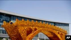 កម្មករកំពុងបំពាក់ខ្សែនៅលើស្ពាន Golden Bridge នៃ Silk Road នៅខាងក្រៅមជ្ឈមណ្ឌលជាតិទីតាំងសម្រាប់វេទិកា Belt and Road សម្រាប់សហប្រតិបត្តិការអន្តរជាតិនៅ ទីក្រុងប៉េកាំងកាលពីថ្ងៃទី១៨ មេសា ២០១៧។