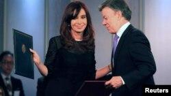 Los presidentes de Argentina, Cristina Fernández, y de Colombia, Juan Manuel Santos, intercambian copias de los acuerdos.