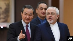 """Iranian Foreign Minister Mohammad Javad Zarif (R) arrives with Chinese Foreign Minister Wang Yi for a joint press conference in Beijing, China, Dec. 5, 2016. Zarif said that nations party to the Iran nuclear deal """"have the obligation to fully implement it"""
