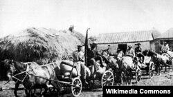 """Tüğyan edən aclığa baxmayaraq, sovet hökuməti zor gücünə kəndlilərdən taxıl yığmaqda davam edirdi. Proletar İnqilabı Kolxozundan """"Qırmızı Qatar"""" adlanan araba kolxozun ilk məhsulunu daşıyıb aparır. Oleksiyivka, Xarkov. 1932."""
