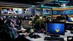 FILE - Employees work in the newsroom of Hezbollah's Al-Manar TV station, in the southern suburb of Beirut, Lebanon, Dec. 10, 2015.
