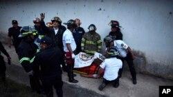 Los bomberos rodean el cuerpo de un hombre dentro de un reformatorio para jóvenes y hombres durante un disturbio en el Centro Correccional Etapa II en San José Pinula, Guatemala, el domingo 19 de marzo de 2017.
