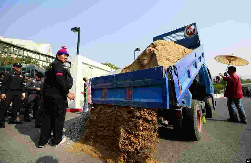 Pro-government supporters dump sand to build a barricade in front of the gate of National Anti-Corruption Commission office in Bangkok, Feb. 27, 2014.