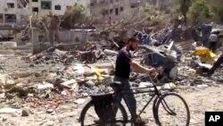 Ảnh chụp từ video đã được kiểm chứng và phù hợp với báo cáo khác của hãng tin AP cho thấy hậu quả của cuộc không kích của chính phủ Syria vào khu dân cư ở Douma, ngoại ô Damascus, ngày 16/8/2015.