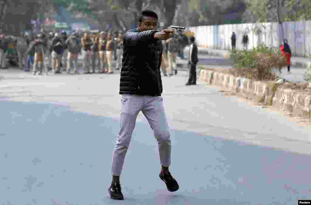 An unidentified man holds up a gun during a protest against a new citizenship law outside the Jamia Millia Islamia university in New Delhi, India.