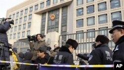 """2010年2月11日中国警察监视正在等候北京最高法院前的记者们,他们报导刘晓波被控以""""煽动颠覆国家政权罪""""被判刑11年的上诉案审理情况。"""