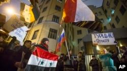 24일 러시아 모스크바 주재 터키대사관 앞에서 시위대가 러시아와 시리아 국기를 들고 '등에 칼을 꽂았다'고 외치고 있다.