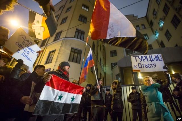 Người biểu tình cầm cờ Nga và Thổ Nhĩ Kỳ cùng với biểu ngữ 'Thổ Nhĩ Kỳ phải chịu trách nhiệm!' và 'Đâm sau lưng - trả lời trước mặt!' trước sứ quán Thổ Nhĩ Kỳ ở Moscow, Nga, ngày 24/11/2015.