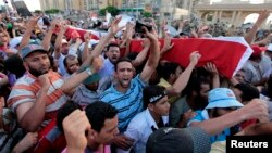 Supporters of deposed Egyptian President Mohamed Morsi carry mock coffins during a symbolic funeral for the four men killed during clashes with police outside the Republican Guard headquarters a day earlier, in Cairo, July 6, 2013.