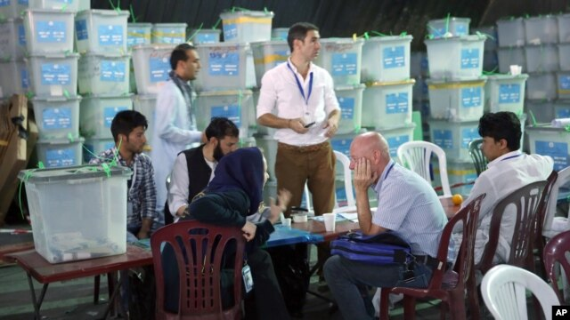 Afghan election commission workers sort ballots for an audit of the presidential run-off votes in front of international observers at an election commission office in Kabul, Aug. 27, 2014.
