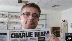 Уредникот на магазинот Чарли Хебдо со насловната страница на магазинот.
