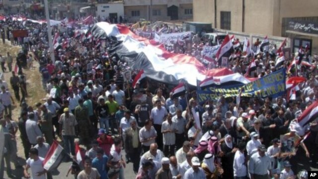 In this photo released by the Syrian official news agency SANA, Syrian pro-government protesters carry national flags along with pictures of Syrian President Bashar Assad during a rally in support of the reform program in the border town of Quneitra, Syri