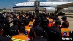 Các công dân Trung Quốc bị tình nghi lừa đảo tống tiền qua mạng (áo khoác da cam) được cảnh sát Trung Quốc áp tải chờ lên máy bay tại Sân bay Quốc tế Phnom Penh, ở Phnom Penh, Campuchia, ngày 12 tháng 10, 2017.