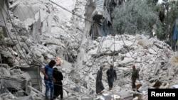 Les gens inspectent un site endommagé après des frappes aériennes sur le quartier Tariq al-Bab tenu par les rebelles, à Alep, Syrie, 23 septembre 2016.