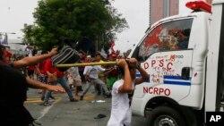 19일 필리핀마닐라 주재 미국대사관앞에서열린 반미시위에서, 참가자들이 경찰 소속 차량을 공격하고 있다.