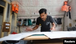 Migrant Abid Ali from Pakistan works as tailor and designer at the non-profit organization Mimycri, which recycles parts of a discarded dinghies into bags, in Berlin, Germany, July 23, 2018.