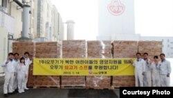 대북지원 쇠고기 수프 물품 앞에서 기념촬영한 한국 식품기업 '오뚜기' 직원들 .