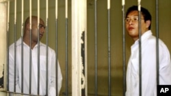Australian Andrew Chan, right, and, and Myuran Sukumaran, left, stand inside a holding cell after their trial at a court in Denpasar, Bali, Indonesia, Tuesday, Feb. 14, 2006.