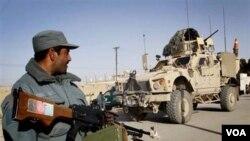 Seorang polisi Afghanistan siaga di dekat kendaraan militer AS di provinsi Kandahar (foto: dok.)