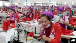 FILE: Garment workers sew clothes in a factory as they wait for visit by Prime Minister Hun Sen outside of Phnom Penh, Cambodia, Wednesday, Aug. 30, 2017. (AP Photo/Heng Sinith)