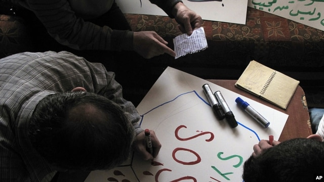 Syrian activists prepare signs for protests at a house in a neighborhood in Damascus, Syria.