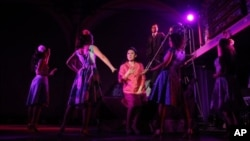 """This undated theater image released by The Public Theater shows Ruthie Ann Miles, center, during a performance of """"Here Lies Love,"""" in New York."""